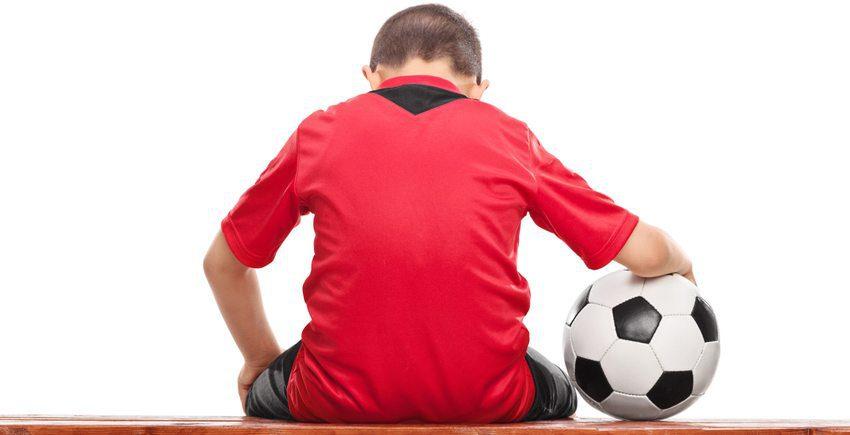 ילד עם כדור על ספסל המחליפים