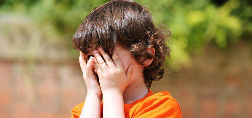 ילד מסתיר עם הידיים את הפנים