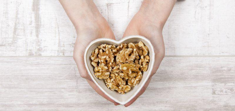 ידיים מחזיקות קערת אגוזי מלך בצורת לב
