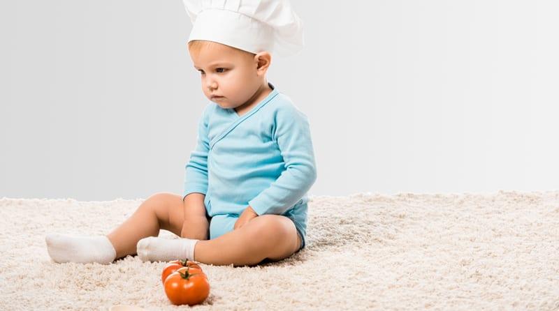 ילד יושב לא מרוצה ליד עגבניה