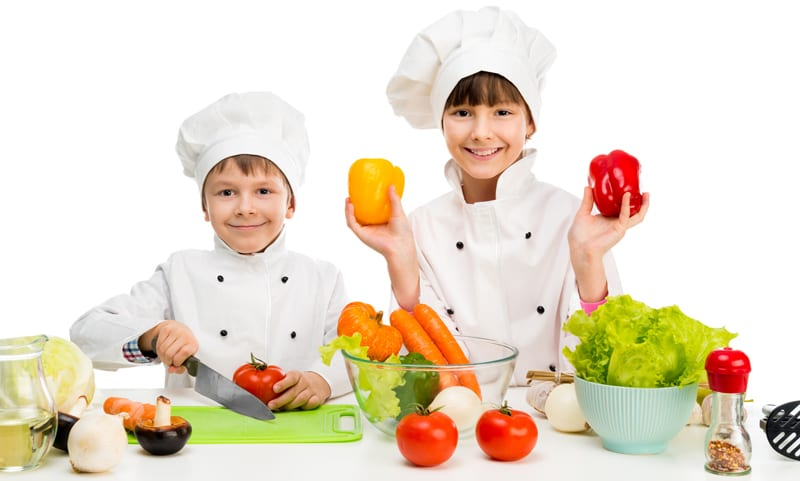 ילדים בבגדי שף חותכים ירקות