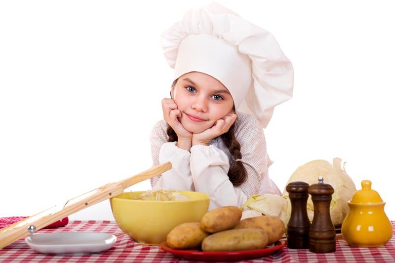 ילדה בלבוש טבחית ותפוחי אדמה על השולחן