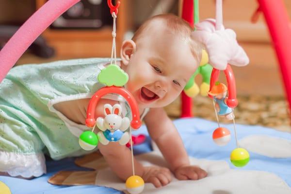 תינוק משחק על שטיחון עם אוניברסיטה