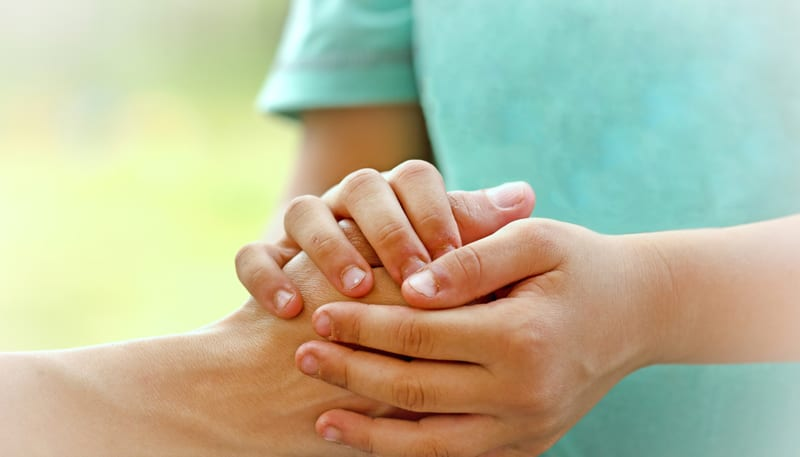 יד של אמא אוחזת בידיים של ילד