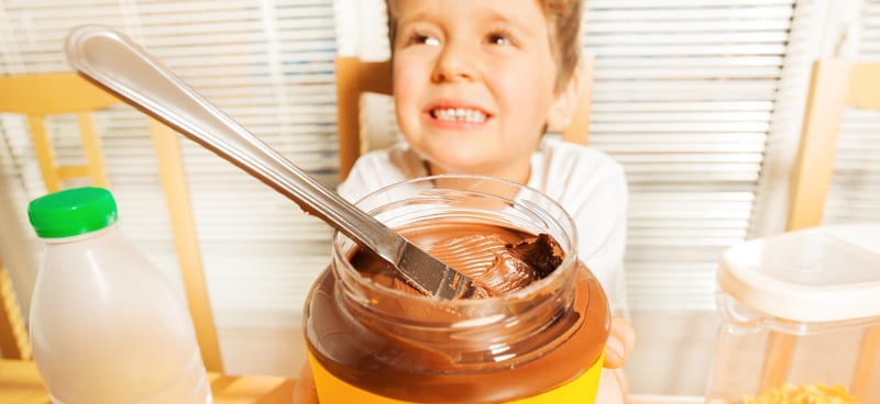 ילד מחזיק קופסת שוקולדת למריחה עם מבט מתחנן