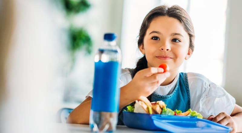 ילדה אוכלת מקופסת אוכל